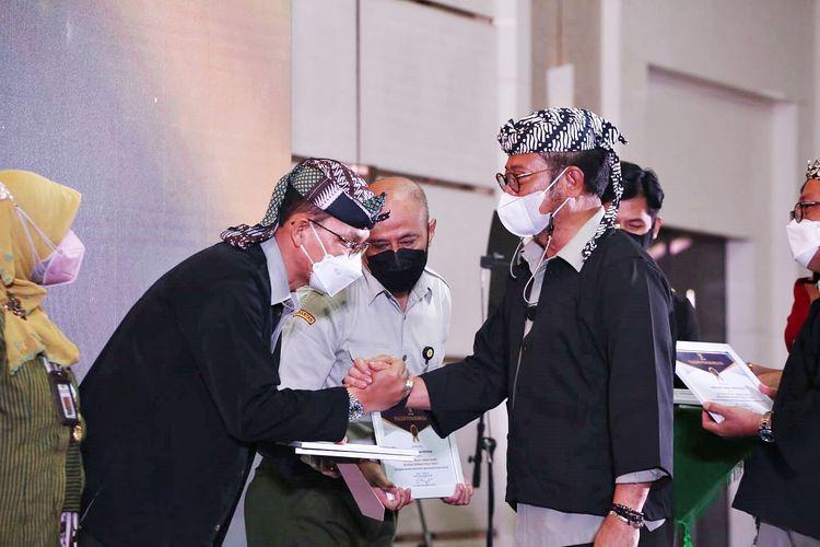 Menteri Pertanian Syahrul Yasin Limpo saat memberikan penghargaan kepada Direktur Jenderal Prasarana dan Sarana Pertanian Kementan Ali Jamil dalam acara Anugerah Keterbukaan Informasi Publik Tahun 2021, Senin (11/10/2021).