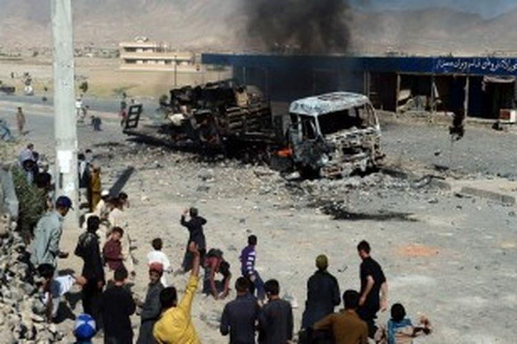 Para demonstran Afganistan melempar batu dan meneriakkan slogan setelah membakar sebuah truk, yang diyakini miliki orang asing, dalam sebuah kerusuhan anti-pemerintah di Kabul pada tanggal 24 Juni 2013. Para demonstran berpartisipasi dalam kerusuhan melawan pemerintah Afganistan setelah sebuah bentrokan antara polisi dan orang-orang bersenjata tak dikenal karena perampasan tanah di timur kota Kabul.