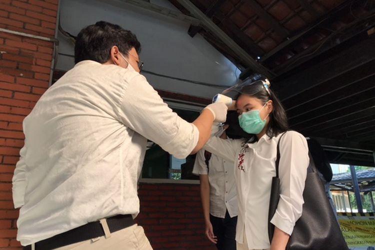 Panitia UTBK SBMPTN 2020 mengukur suhu peserta sebelum masuk ruang ujian di Fakultas Ilmu Pengetahuan Budaya Universitas Indonesia (FIB UI), Depok, Jawa Barat, Minggu (5/7/2020).