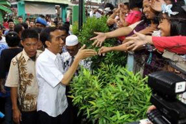 Gubernur DKI Jakarta Joko Widodo disambut warga yang berebut ingin bersalaman dengannya saat ia akan masuk ke SMP Negeri 108, Cengkareng, Jakarta Barat, Kamis (25/4/2013). Jokowi berkunjung ke SMPN 108 untuk bersilaturahim dan memberi arahan kepada siswa yang baru selesai melaksanakan Ujian Nasional (UN).