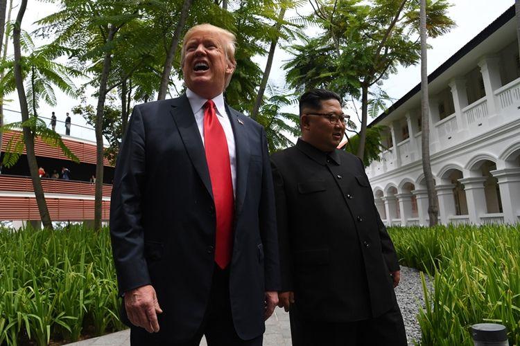 Presiden AS Donald Trump (kiri) berjalan bersama Pemimpin Korea Utara Kim Jong Un menuju lokasi penandatanganan dokumen usai makan siang bersama.