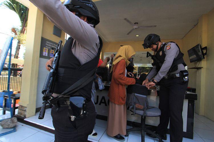 Petugas kepolisian memeriksa warga yang akan masuk ke Mapolres Indramayu, Jawa Barat, Senin (14/5/2018). Petugas memperketat penjagaan kawasan Markas Polres Indramayu pascaledakan bom di sejumlah titik di Surabaya.