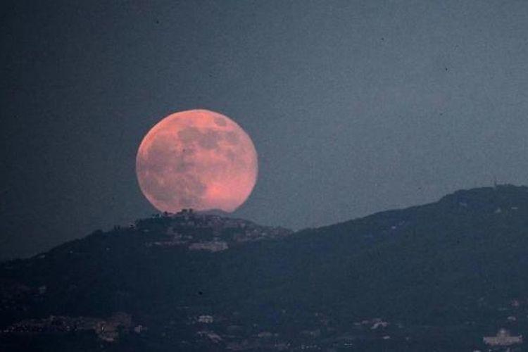 Bulan purnama terbit di atas kota Roma, 23 Juni 2013. Bulan yang akan mencapai tahap penuh pada Minggu, 14 persen lebih dekat ke bumi dan dikenal sebagai fenomena supermoon.
