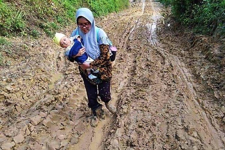 Khatimah, guru menggendong bayinya menuju SMP 4 Pante Bidari, di Desa Sijudo, Kecamatan Pante Bidari, Kabupaten Aceh Timur