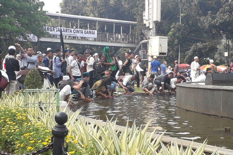 Massa aksi mengambil wudhu di kolam air mancur Patung Arjuna Wiwaha atau Patung Kuda, Kamis (27/6/2019) sore.