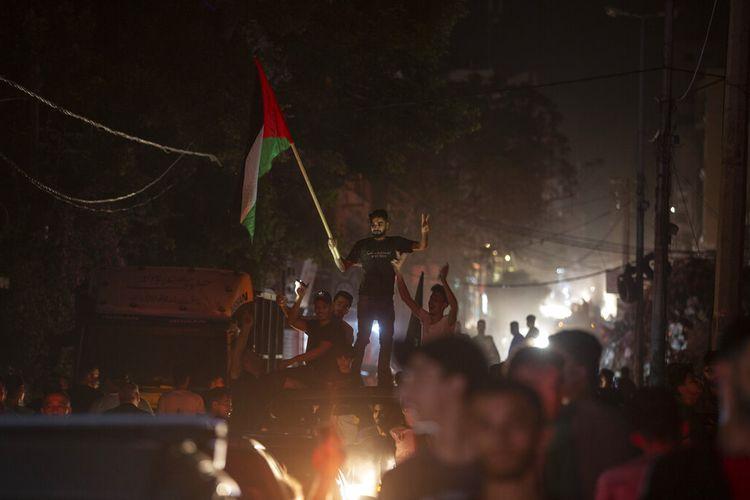 Warga Palestina meneriakkan slogan-slogan merayakan gencatan senjata yang dicapai setelah perang 11 hari antara Hamas dan Israel di Gaza City, Jumat (21/5/2021).