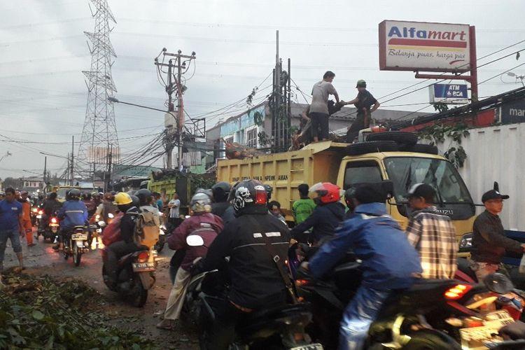 Petugas mengevakuasi pohon tumbang di Jalan Raya Dermaga, Duren Sawit, yang menewaskan satu orang pengendaea, Selasa (2/4/2019).