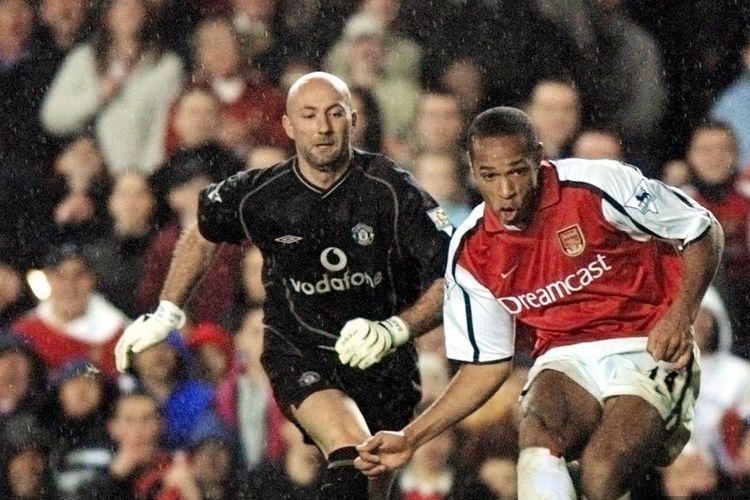 Thierry Henry berduel dengan Fabien Barthez pada laga Liga Ingris di Stadion Highbury pada 25 November 2001.