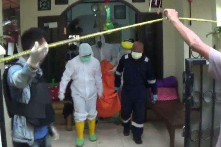 Petugas berpakaian APD mengevakuasi suami istri yang ditemukan meninggal dunia di rumahnya di Jatiasih, Kota Bekasi, Senin (27/4/2020).