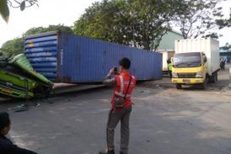 Sebuah truk kontainer dengan nomor polisi B 9095 UEL terguling di Jalan Yos Sudarso, Jakarta Utara Senin, (7/7/2014) siang.