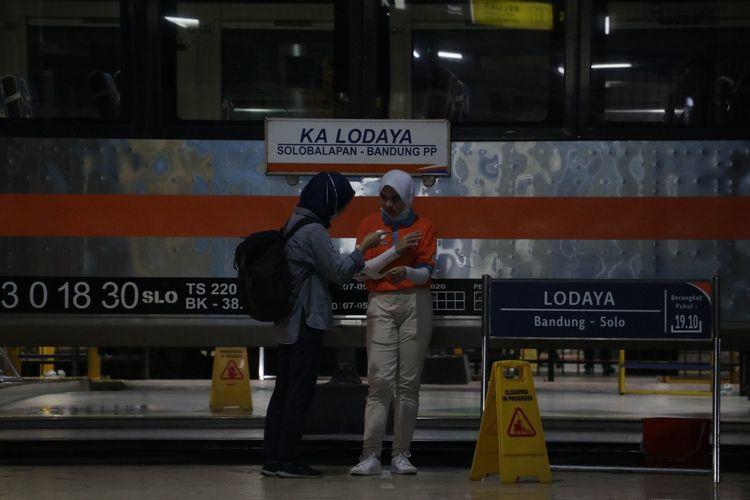 Seorang penumpang tengah meminta bantuan petugas menunjukkan kereta yang akan ditumpanginya.