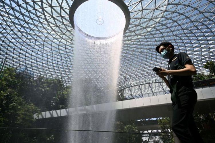 Seorang pengunjung terlihat memakai masker di depan objek wisata teranyar Singapura, air terjun Rain Vortex di Jewel Changi Airport. Air terjun dalam ruangan setinggi 40 meter ini diklaim merupakan yang terbesar di dunia.