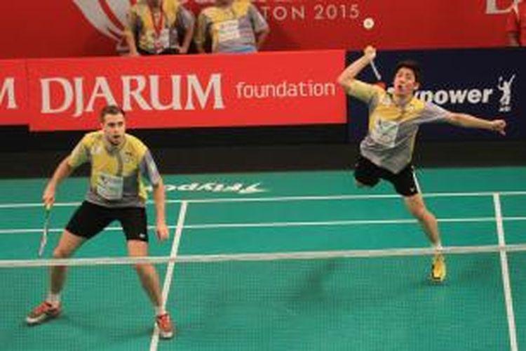 Pemain ganda Musica Champion Kudus, Lee Yong-dae/Vladimir Ivanov, melakukan serangan saat menghadapi Pakkawat Vilailak/Watchana Buranakuea (Granular Thailand) pada lanjutan babak penyisihan grup Djarum Superliga Badminton 2015 di Denpasar, Rabu (28/1/2015). Lee/Ivanov menang 21-14, 21-14.