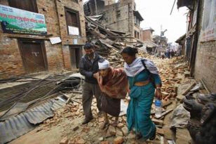 Warga lanjut usia dibantu melintasu jalanan yang tertutup puing reruntuhan bangunan setelah diguncang gempa berkekuatan 7.9 SR di Bhaktapur, Kathmandu, Nepal, 26 April 2015.