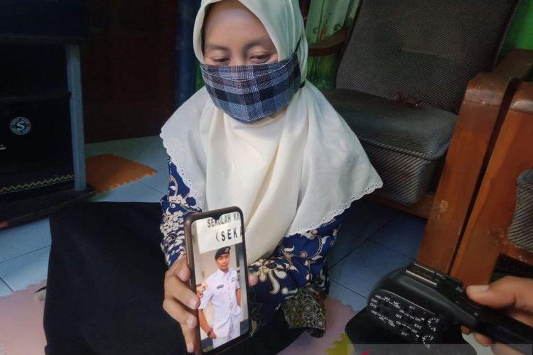 Helen menunjukkan foto suaminya, Serda Diyut yang tercatat sebagai salah satu ABK KRI Nanggala-402 yang hilang di perairan sekitar 60 mil laut utara Pulau Bali, Rabu (21/4/2021) dini hari, di rumahnya Kota Madiun, Jatim, Kamis (22/4/2021).