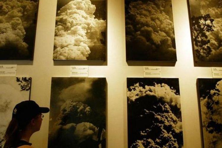 Pengunjung mengamati foto-foto ledakan nuklir di museum dan memorial perdamaian Hiroshima