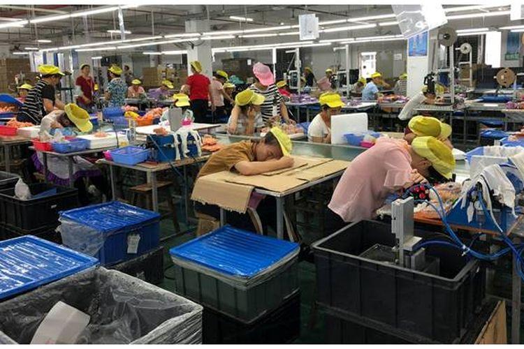 Beberapa pekerja perempuan beristirahat karena merasa kelelahan karena jam kerja yang panjang di pabrik pembuat boneka. Wah Tung di China