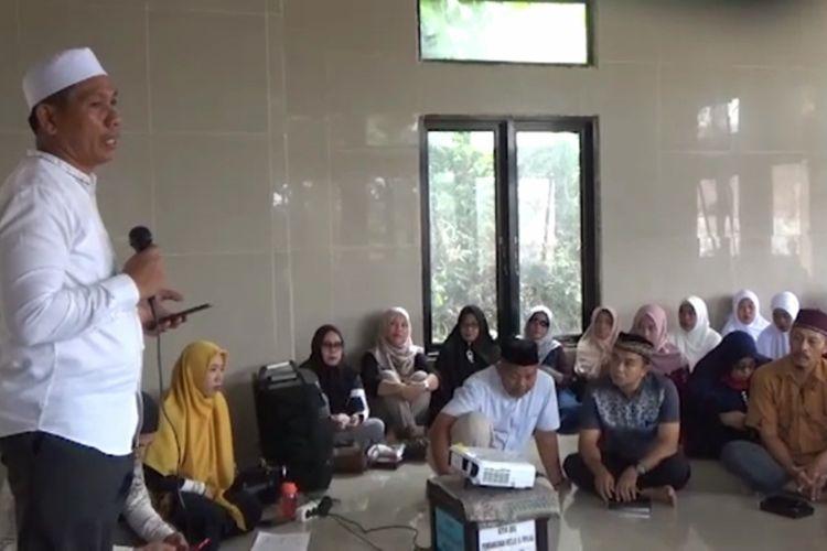 Kemenag Pasangkayu kumpulkan warga dan tokoh masyarakat untuk sosialisasi soal shalat berjamaah di rumah untuk hindari penyebaran Covid-19, Sabtu (11/4/2020). Ironisnya, para warga duduk berdekatan dan tidak mengenakan masker. Tampak Kepala Kemenang Pasangkayu Mustafa memberikan arahan ke warga,