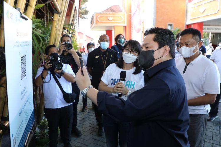 Menteri BUMN Erick Thohir (tengah) didampingi Direktur Utama Telkom Ririek Adriansyah (kanan) melakukan check-in digital dengan scan QR Code PeduliLindungi sebelum memasuki lokasi UMKM saat kunjungan kerja di Denpasar pada Senin, (20/9/2021).