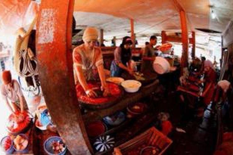 Para ibu-ibu menjadi tenaga ojek menggiling cabai di Pasar Payahkumbuh, Sumatera Barat, Rabu (10/7/2013). Jasa penggilingan cabai (manggiliang lado) ini Rp 3500 per kilogram cabai. Dalam sehari para tenaga ojek penggiling cabai ini mengerjakan orderan sekitar 15 kilogram cabai.