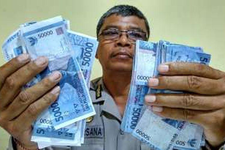 Petugas menunjukan Barang bukti uang palsu pecahan Rp 50.000