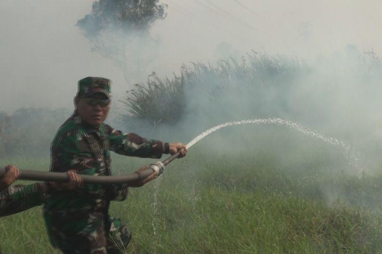 Panglima Komando Daerah Militer II Sriwijaya Mayor Jendral TNI AM Putranto ikut terjun langsung memadamkan api dengan menyemprotkan air ke lahan yang terbakar, Minggu (6/8/2017).