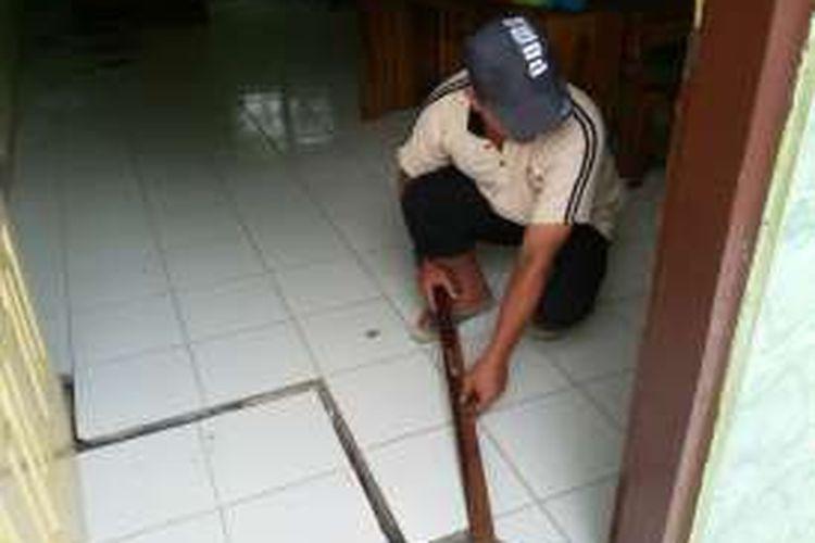 Foto : Penjaga SDN 02 Tugurejo, Yudi Purnanto menunjukkan lantai yang merekah akibat tanah bergerak di salah satu ruang kelas, Senin (5/12/2016)