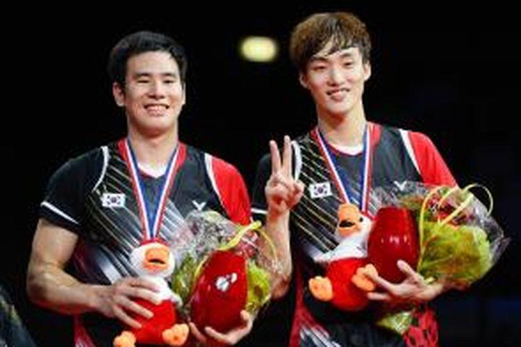 Pasangan ganda putra Korea, Ko Sung-hyun (kiri)/Shin Baek-cheol, berpose di atas podium tertinggi setelah meraih kemenangan atas sesama ganda Korea, Lee Yong-dae/Yoo Yeon-seong, pada final Kejuaraan Dunia 2014 di Ballerup Super Arena, Kopenhagen, Denmark, Minggu (31/8/2014).