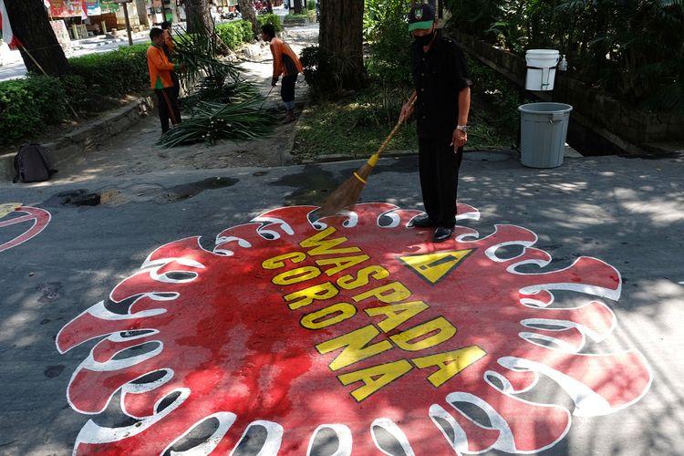 Pekerja membersihkan jalan yang terdapat mural berisi pesan Waspada Penyebaran Virus Corona di halaman Kantor Dinas Lingkungan Hidup, Solo, Jawa Tengah, Senin (3/8/2020). Mural tersebut dibuat agar pengguna jalan mematuhi protokol kesehatan guna mencegah penyebaran COVID-19. ANTARA FOTO/Maulana Surya/wsj.