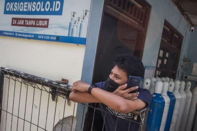 Pekerja menelepon distributor oksigen untuk mendapatkan pasokan di agen tabung oksigen, Pusang Sawit, Solo, Jawa Tengah, Kamis (01/07).