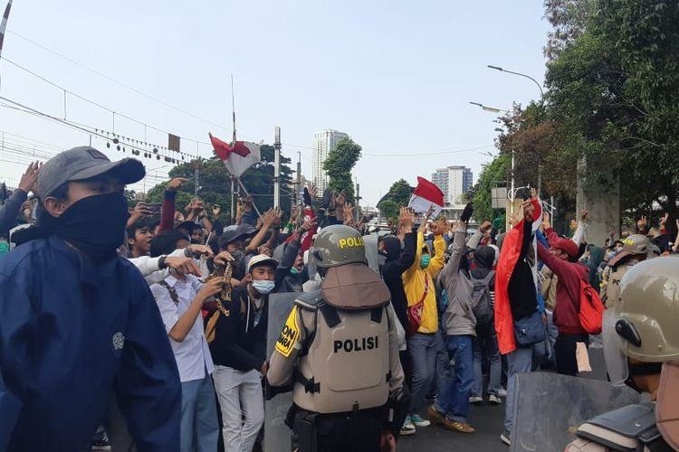 Puluhan pelajar dari berbagai sekolah mulai memadati area perlintasan sebidang rel kereta di Stasiun Palmerah, Senin (30/9/2019). Di depan polisi yang bertugas mereka bernyanyi, dengan membawa bendera.