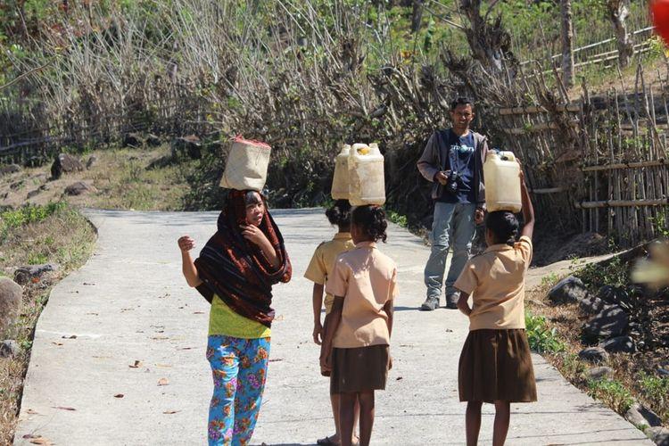Siswa-siswi SDI Tuanio, Desa Pagomogo, Kecamatan Nangaroro, Kabupaten Nagekeo, Flores, NTT memikul air ke sekolah, Senin (14/10/2019). Mereka harus berjalan 5 km setiap hari dengan memikul air di atas kepala menuju sekolah.