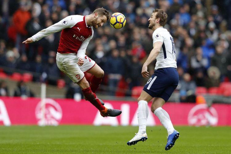 Shkodran Mustafi menghalau bola dari kejaran Harry Kane saat Arsenal berhadapan dengan Tottenham Hotspur pada laga Premier League di Wembley, Sabtu (10/2/2018).