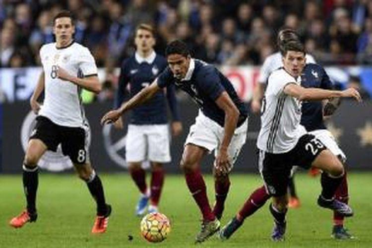 Bek Prancis Raphael Varane (tengah) bersaing merebut bola dengan pemain Jerman Mario Gomez (kanan) pada laga persahabatan di Stadion Stade de France, Jumat (13/11/2015) waktu setempat.