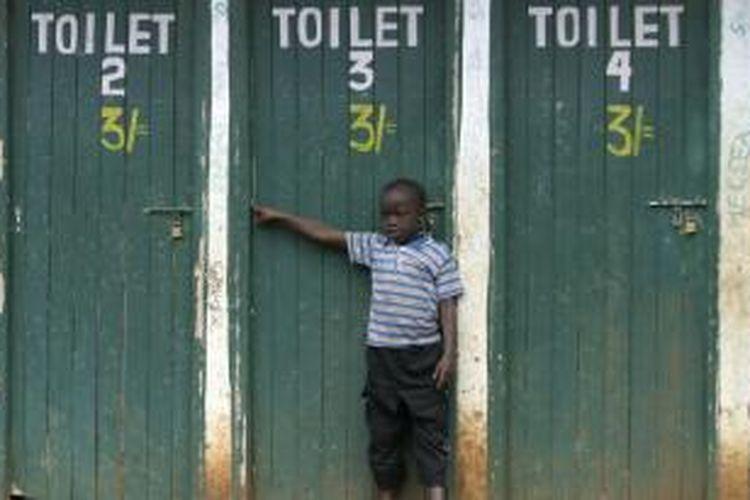 Seorang anak laki-laki sedang berdiri di toilet publik Nairobi.