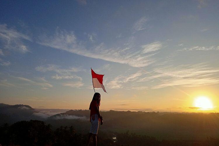 Seorang pengunjung berfoto dengan latar matahari terbit di Lapangan Pasola Hoba Kalla, Desa Patiala Bawa, Kecamatan Lamboya, Kabupaten Sumba Barat, Nusa Tenggara Timur (NTT).