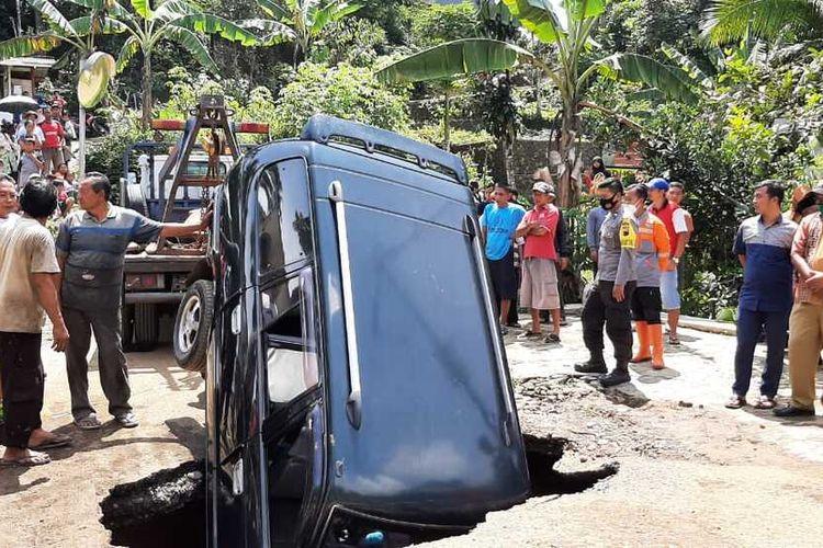 Petugas menarik mobil yang terperosok di Jalan Kaliwiro-Selomanik, Kecamatan Kaliwiro, Kabupaten Wonosobo, Jawa Tengah, Selasa (16/2/2021)