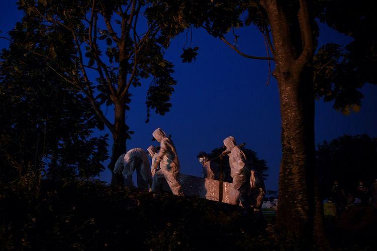 Petugas yang mengenakan APD membawa peti berisi jenazah dengan protokol COVID-19 di TPU Srengseng Sawah, Jakarta, Kamis (21/1/2021). TPU Srengseng Sawah yang baru sepekan dibuka untuk pemakaman dengan protokol COVID-19 dan menyediakan 541 liang lahat hampir penuh karena tingginya jumlah kematian akibat COVID-19. ANTARA FOTO/Wahyu Putro A/foc.