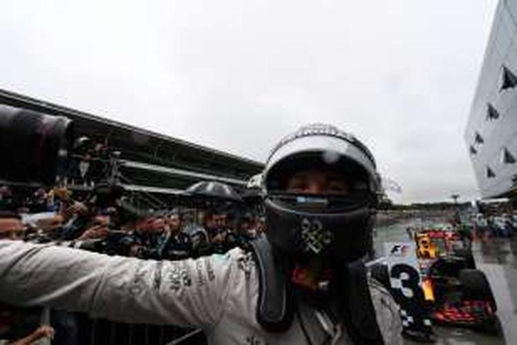 Pebalap Mercedes AMG Petronas F1 Team asal Inggris, Lewis Hamilton, merayakan kemenangan setelah finis di urutan pertama pada balapan GP Brasil di Autodromo Jose Carlos Pace, Interlagos, Minggu (13/11/2016).