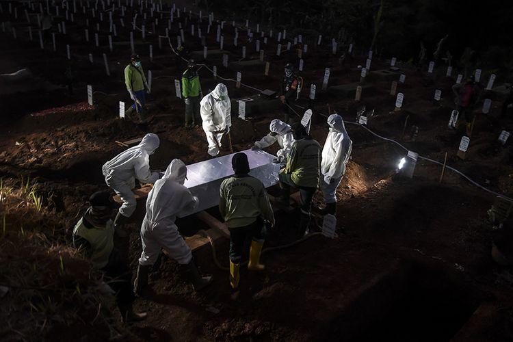 Foto dirilis Sabtu (19/9/2020), memperlihatkan petugas penggali makam jenazah Covid-19 menurunkan peti ke dalam liang lahat di kompleks pemakaman Pondok Ranggon. Selain tenaga medis yang menjadi garda terdepan penanganan virus corona, salah satu pahlawan lain juga patut diberikan apresiasi tinggi adalah petugas pemakaman jenazah Covid-19.