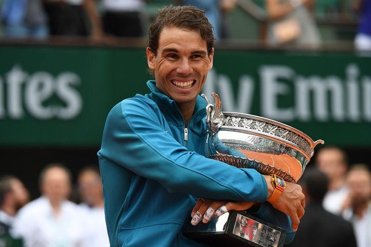 Petenis Spanyol, Rafael Nadal, berpose dengan trofi Perancis Terbuka 2018 yang dia raih setelah menang atas pemain Austria, Dominic Thiem, Minggu (10/6/2018). Ini menjadi gelar ke-11 Nadal di Roland Garros.