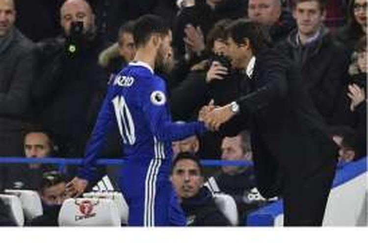 Gelandang Chelsea, Eden Hazard (kiri), bersalaman dengan manajer Antonio Conte, setelah ditarik keluar dalam pertandingan Premier League melawan Everton di Stamford Bridge, London, Sabtu (5/11/2016). Chelsea menang 5-0 dan Hazard mencetak dua gol.