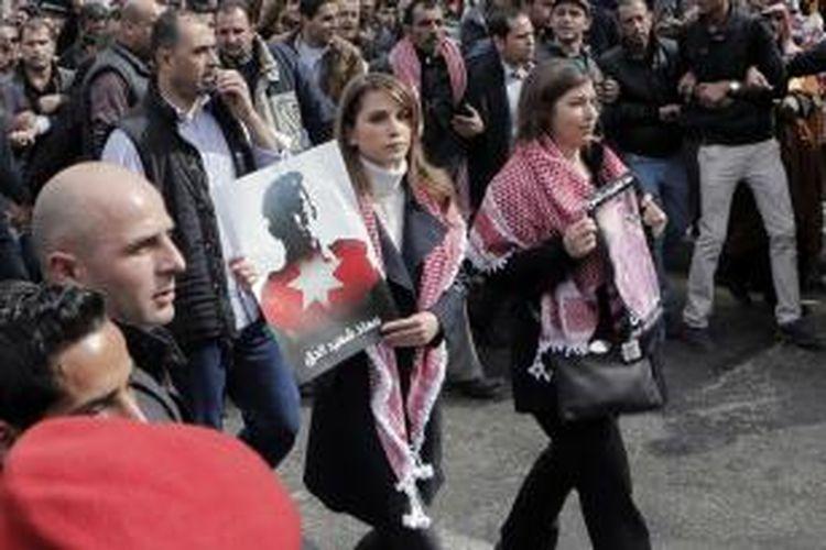 Ratu Rania, istri Raja Abdullah dari Jordania, ikut membawa poster dalam unjuk rasa menentang ISIS dan mendukung keluarga pilot muda Maaz al-Kassasbeh di Amman, Jumat (6/2/2015).