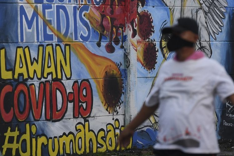 Seorang warga berolah raga dengan latar belakang mural ajakan melawan COVID-19 di Depok, Jawa Barat, Selasa (14/4/2020). Pemprov Jawa Barat akan memulai pembatasan sosial skala besar (PSBB) di Bogor, Depok, Bekasi sebagai kota penyangga Ibu Kota pada Rabu (15/4) dengan menyiapkan anggaran Rp4 triliun sebagai jaring pengaman sosial. ANTARA FOTO/Wahyu Putro A/foc.
