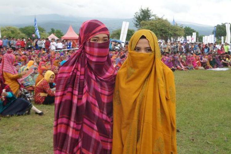 Dua perempuan suku Mbojo diabadikan saat menghadiri acara pembuka Festival Pesona Tambora di Doro Ncanga, Kabupaten Dompu, Nusa Tenggara Barat, Jumat (15/4/2016). Perempuan suku Mbojo yang belum menikah mengenakan rimpu atau balutan kain tanpa memperlihatkan wajah mereka seutuhnya, sedangkan yang telah menikah, rimpu dipasang tidak menutup wajah.