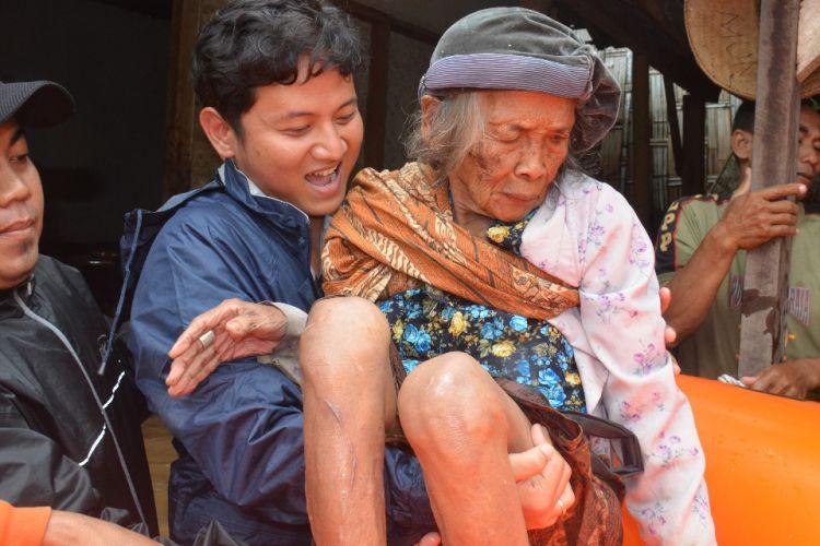 Plt. Bupati Trenggalek Mochammad Nur Arifin Mengevakuasi orang lansia dengan cara digendong menuju ke tempat yang lebih aman, yang berada di desa Kranding Kabupaten Trenggalek Jawa Timur.