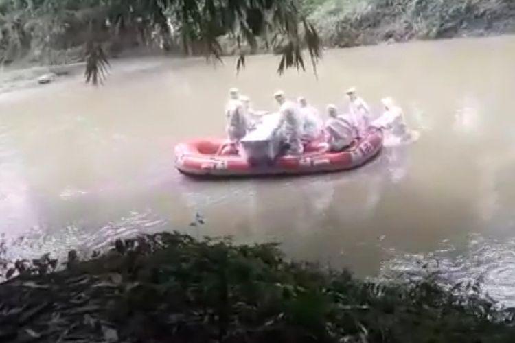 Petugas pengantar jenazah Covid-19 Kota Padang mengantarkan jenazah menyeberangi sungai ke pemakaman, Jumat (17/4/2020) lalu
