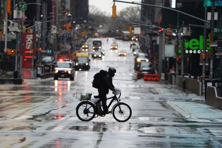 Pengantar barang mengendarai sepedanya menyeberangi 7th Avenue di kawasan Times Square yang kosong akibat meluasnya penularan virus COVID-19, di wilayah Manhattan, New York, Amerika Serikat, Senin (23/3/2020).
