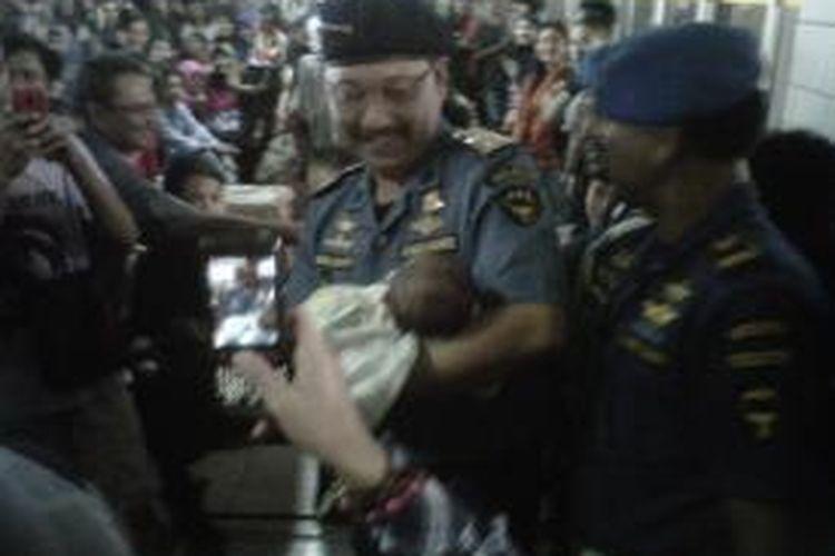 Di sela-sela kunjungan untuk memantau arus mudik di Pelabuhan Makassar, Wamen Perhubungan, Bambang Susanto menggendong seorang bayi yang masih berusia tiga minggu yang juga ikut menunggu kedatangan kapal bersama orangtuanya, Rabu (31/7/2013).