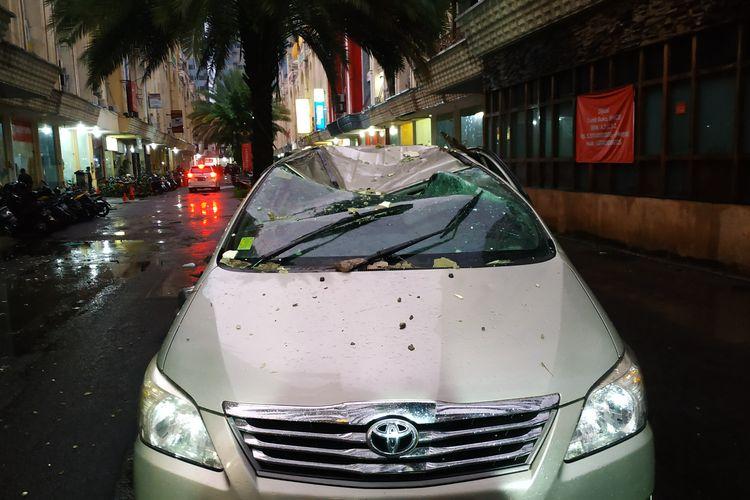 Mobil ringsek di area pertokoan Saladdin akibat tertimpa panel bangunan ketika hujan deras dan angin kencang melanda kota Depok pada Selasa (21/9/2021) sore.